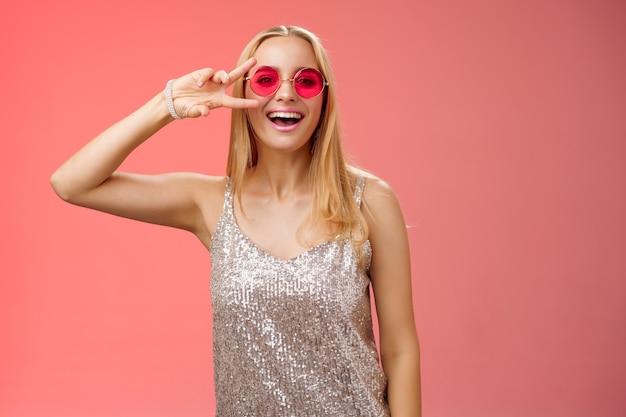 シルバーのスタイリッシュなドレスサングラスを身に着けた元気でフレンドリーな格好良い金髪の25代の女性は、平和の勝利のジェスチャーを示していますのんきな笑顔のカメラは、赤い背景に立って、クールなパーティーを楽しんで楽しんでいます。