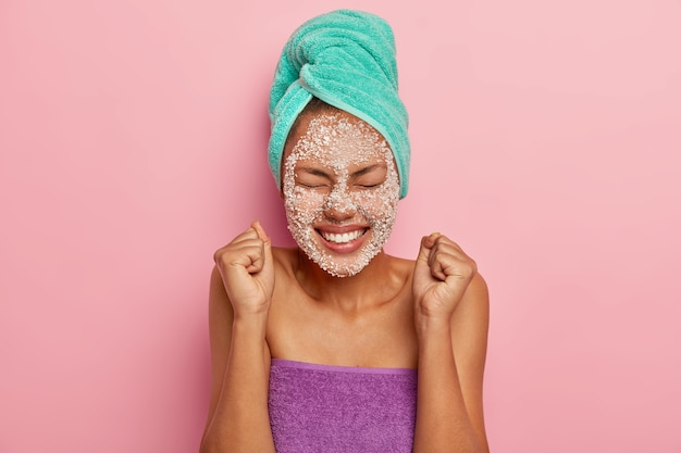Energized happy  female model raises clenched fists, rejoices pleasant moment in life, has eyes closed, toothy smile, applies sea salt srcub mask on complexion for reducing fine lines