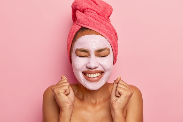 Energized happy woman wears clay mask on face, wrapped towel on hair, smiles broadly, clenches fists from pleasure, isolated over pink wall