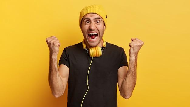 Энергичный мужчина громко кричит, сжимает кулаки, веселится в помещении
