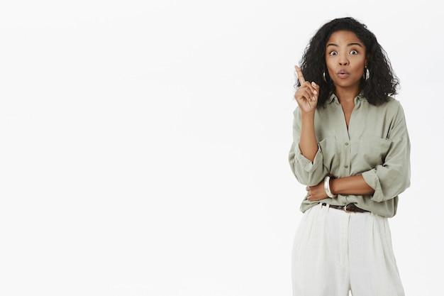 Donna energizzata intelligente e creativa che alza il dito indice