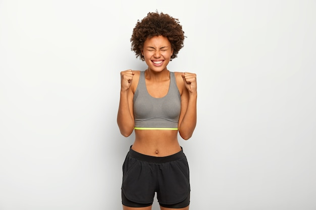 Energized sporty woman rejoices winning, raises clenched fists, smiles broadly, wears sport bra, smiles broadly, isolated over white background,