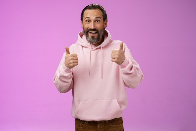 Energized supportive happy charming hipster mature guy bearded grey hair show thumbs up gesture yes approval sign totally agree cheering root for friend like awesome idea, standing purple background.