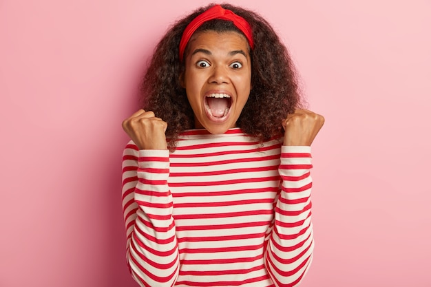 Energized teenage girl with curly hair posing in striped red sweater
