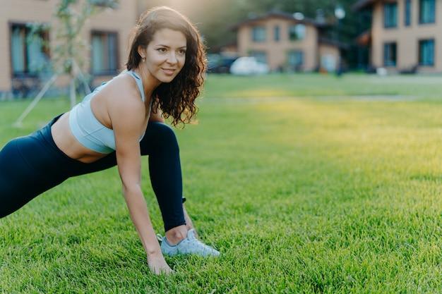 トップとレギンスで元気な女性は、屋外の晴れた日の間に緑の芝生でストレッチ運動をします