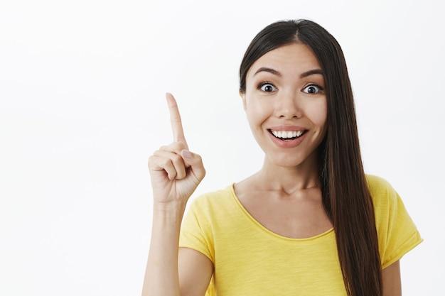 Giovane genio femminile creativo eccitato con un ampio sorriso bianco che alza il dito indice nel gesto di eureka