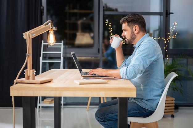 エネルギッシュなドリンク。ラップトップの画面を見て、コーヒーを飲みながら仕事に集中している素敵なインテリジェントな勤勉な男