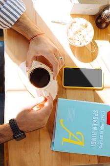 활력을주는 음료. 테이블에 앉아있는 동안 남성 손에 커피 컵의 상위 뷰