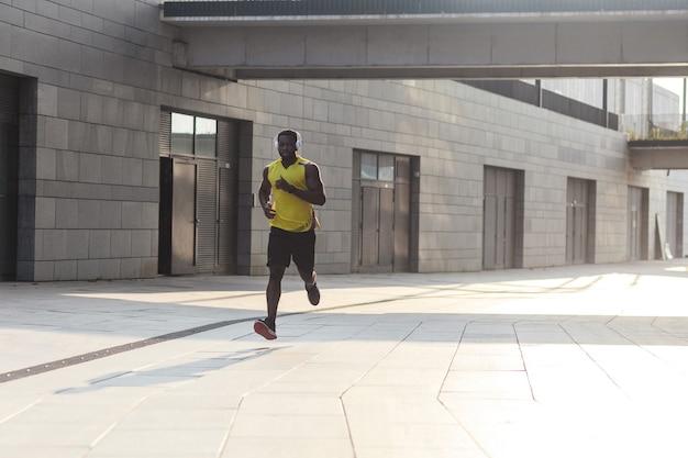 Энергичный афро-американский бегун тренируется и бегает в летний день на открытом воздухе в спортивной одежде желтого цвета