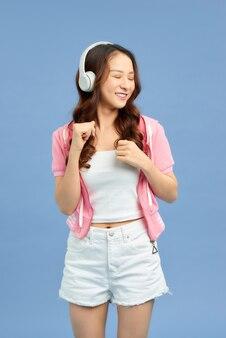 헤드폰을 끼고 스튜디오에서 파란 배경에 눈을 감고 음악을 듣고 있는 에너지 아시아 소녀. 그녀는 흰색 티셔츠, 반바지를 입는다.