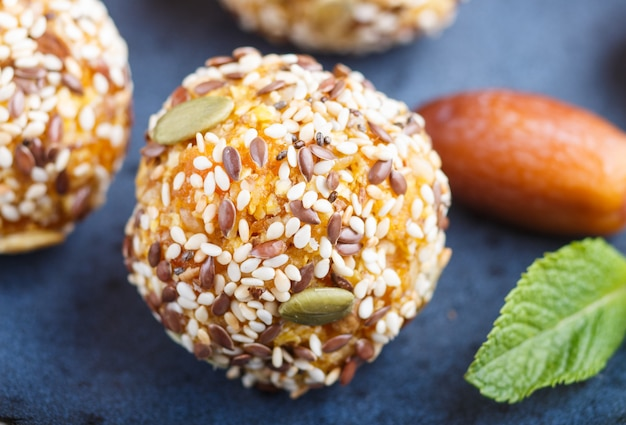 Energy ball cakes with dried apricots, sesame, and dates on a blue ceramic plate, side view.