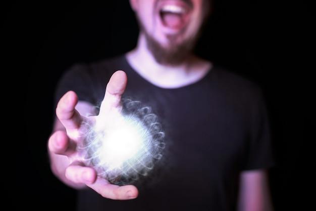 마법사의 손에 있는 에너지 볼. 수염난 남자가 밝은 마법의 공 주문을 시전합니다. 검정색 배경