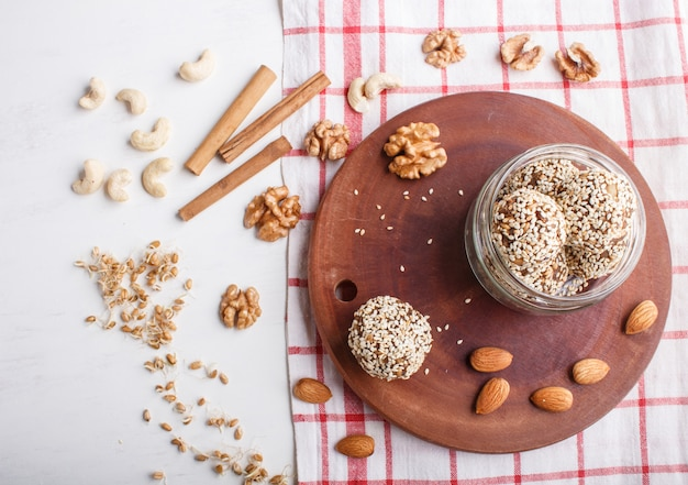 Energy balls cakes with almonds, sesame, cashew, walnuts, dates and germinated wheat in glass jar