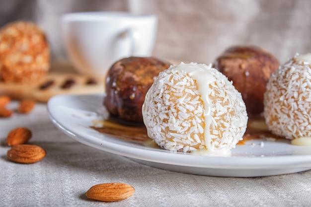 エネルギーボールは、チョコレートキャラメルとリネンのナプキンに白い皿にココナッツケーキします。