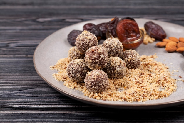 Energy balls in nut crumbs close-up on plate in the manufacturing process.