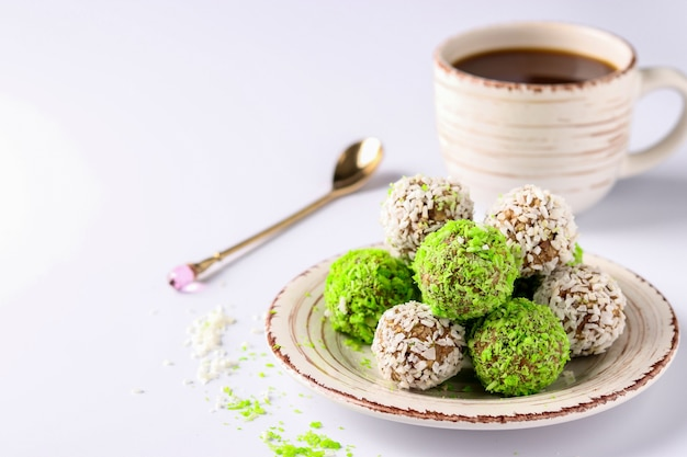 Energy balls of nuts, oatmeal and dried fruits, sprinkled with green and white coconut flakes as well as cup of coffee on white background