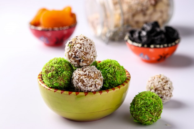 Energy balls of nuts, oatmeal and dried fruits, sprinkled with green and white coconut flakes on a plate