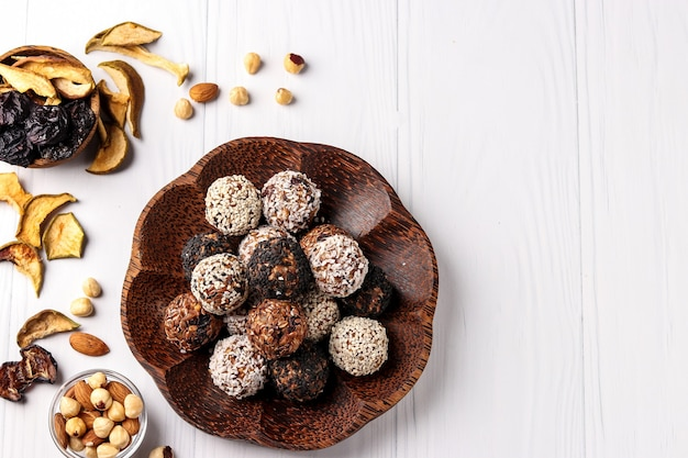 Energy balls of nuts, oatmeal and dried fruits with flax and sesame seeds, coconut flakes on a wooden plate of coconut on a white background, horizontal orientation, top view