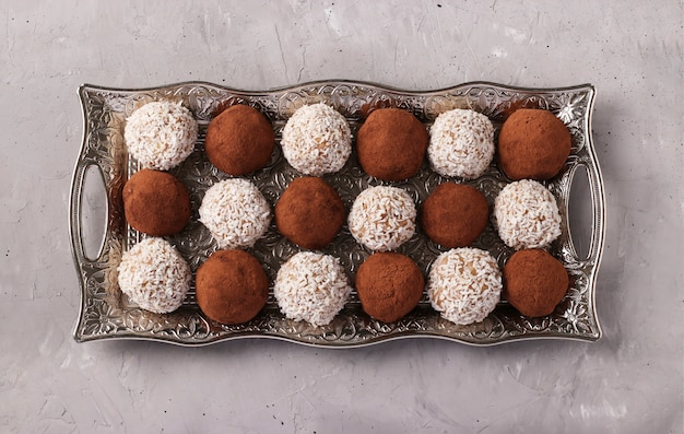 Energy balls of nuts and oatmeal with coconut and cocoa on a metal tray on a gray concrete surface, horizontal format, top view