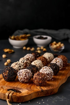 Energy balls of nuts, oatmeals and dried fruit on dark background