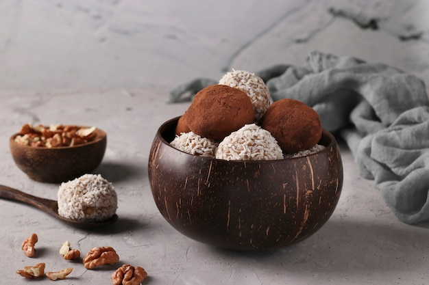 Energy balls of nuts and oatmeals with coconut flakes and cocoa in coconut bowl on gray surface, horizontal format, closeup