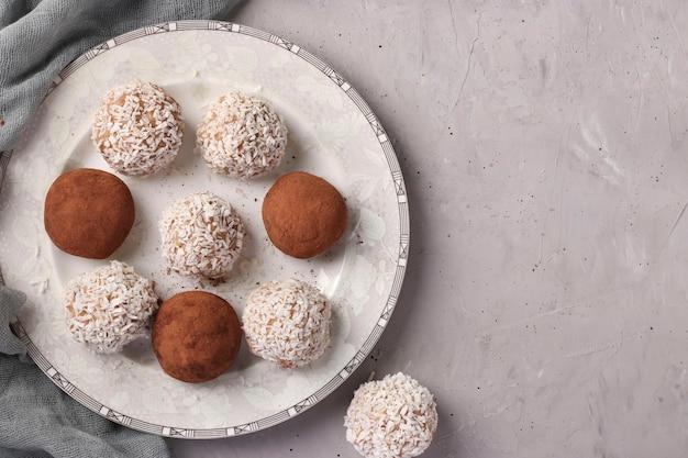 灰色の白いプレートにココナッツフレークとココアが入ったナッツとオートミールのエネルギーボール