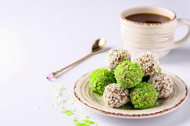 견과류, 오트밀, 말린 과일의 에너지 볼, 녹색 및 흰색 코코넛 플레이크와 흰색 배경에 커피 한 잔을 뿌렸습니다.