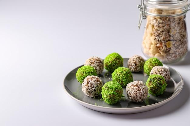 プレートに緑と白のココナッツフレークをまぶしたナッツ、オートミール、ドライフルーツのエネルギーボール
