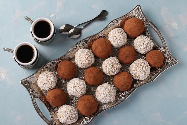 金属製のトレイにナッツ、オートミール、ココナッツ、ココアのエネルギーボール、水色の背景に2杯のコーヒー。上面図、クローズアップ