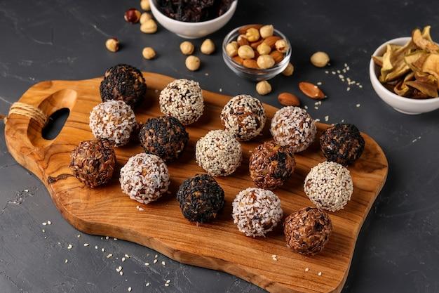 Энергетические шары из орехов, овсяных хлопьев и сухофруктов на деревянной доске на темной поверхности, горизонтальная ориентация, крупным планом