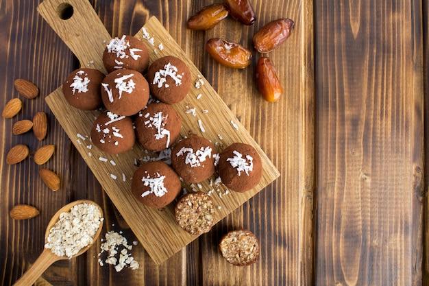 茶色の木の背景のまな板にココナッツチップス、アーモンド、オーツ麦シリアルと日付のエネルギーボール。上面図。コピースペース。