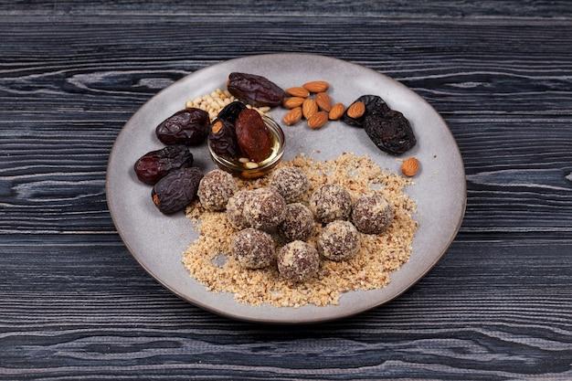 暗い背景に自家製の日付のお菓子の適切な栄養とエネルギーボール