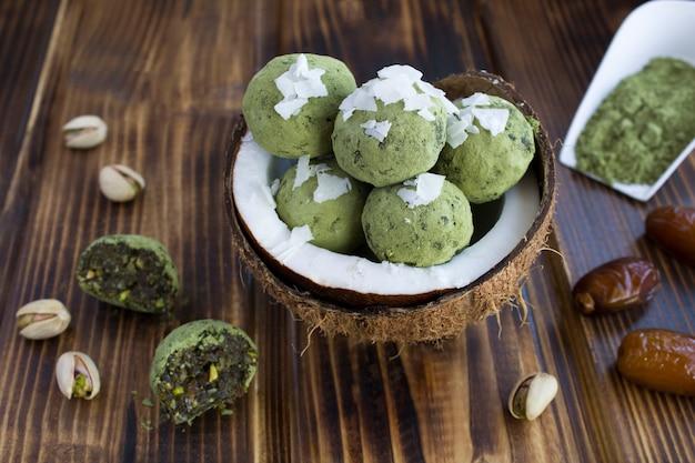 抹茶パウダー、ピスタチオ、ナツメヤシ、ココナッツチップを半分のココナッツに詰めたエネルギーボール