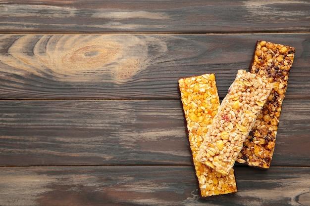 Бары энергии - закуска для здорового натюрморта с космосом экземпляра на коричневой предпосылке.