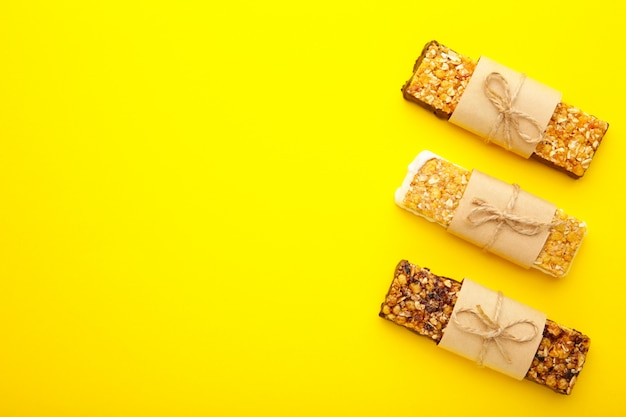 Энергетические батончики - закуска для здорового натюрморта с копией пространства на желтом фоне.