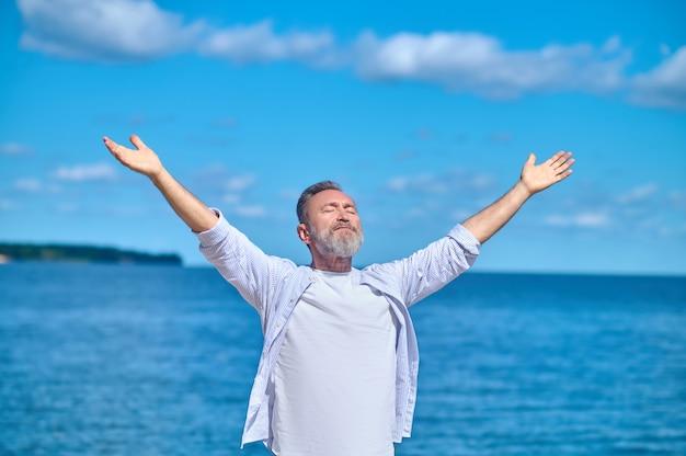 Энергия. бородатый взрослый мужчина с закрытыми глазами с раскинутыми руками в стороны, стоящий на фоне голубого неба и моря в прекрасный день