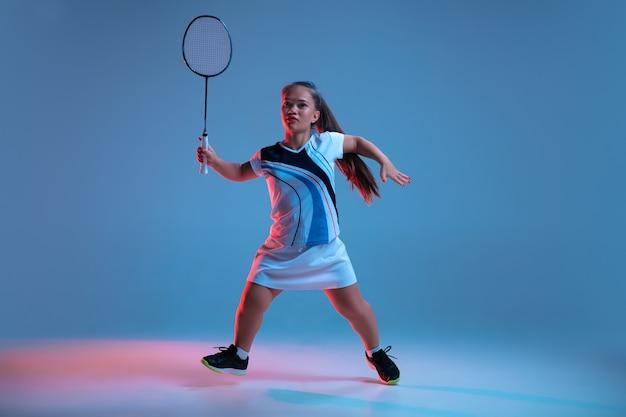 에너지. 네온 불빛에 파란색 배경에 고립 된 배드민턴에서 연습 하는 아름 다운 난쟁이 여자. 포용적인 사람들의 라이프스타일, 다양성과 평등. 스포츠, 활동 및 움직임. 카피스페이스.