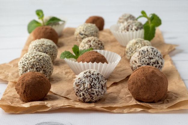 Energy bites with cocoa powder, sesame seeds and coconut flakes on parchment