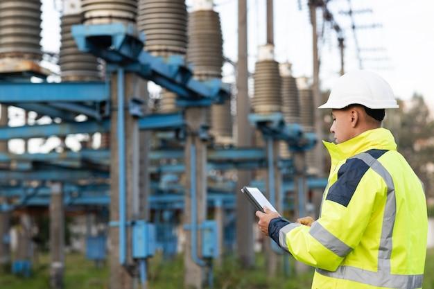 タブレットで読書を勉強しているエネルギービジネス技術業界の概念電気技師