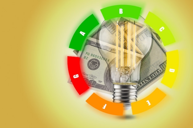 Концепция энергоэффективности светодиодных ламп. снижение потребления электроэнергии. светодиодная лампочка с долларами на желтом фоне. круглый стол.
