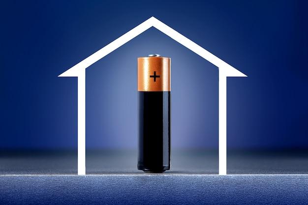 Концепция энергоэффективного дома. батарея с полной энергией и эскиз дома на синем фоне.