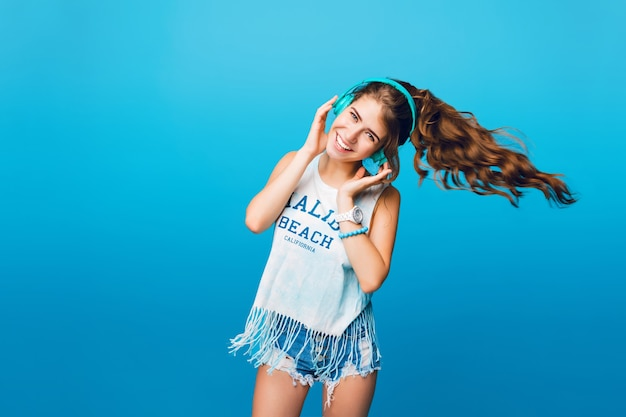 Energy girl with blue headphones  listening to music on blue background in studio. she wears white t-shirt, shorts. long curly hair in tail is flying to side from move.