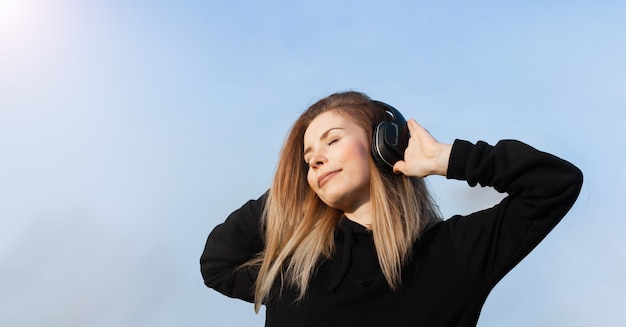 파란색 벽에 닫힌 된 눈으로 음악을 듣고 블루 헤드폰 에너지 소녀. 그녀는 검은 색 후디를 입는다. 꼬리에 긴 곱슬 머리가 움직이면서 날아간다.