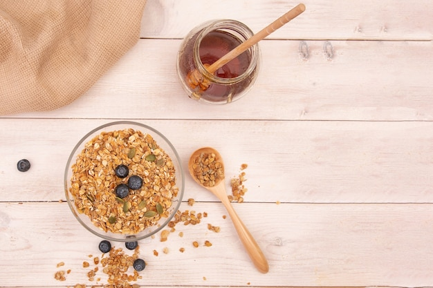 木製のテーブルの上に蜂蜜と透明なボウルのエネルギーグラノーラ。上面図。