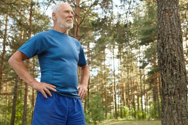 에너지, 건강, 웰빙, 활동 및 스포츠 개념. 소나무 사이에 서, 숲에서 신체 운동을 즐기는 그의 허리에 손을 유지하는 스포츠웨어에 집중된 운동 수석 남자