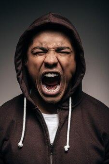 Энергия внутри него. разъяренный молодой африканец в рубашке с капюшоном с закрытыми глазами и криком
