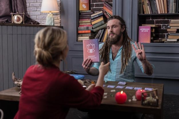 건강의 에너지. 책에 대해 말하는 동안 그의 클라이언트를보고 좋은 잘 생긴 남자