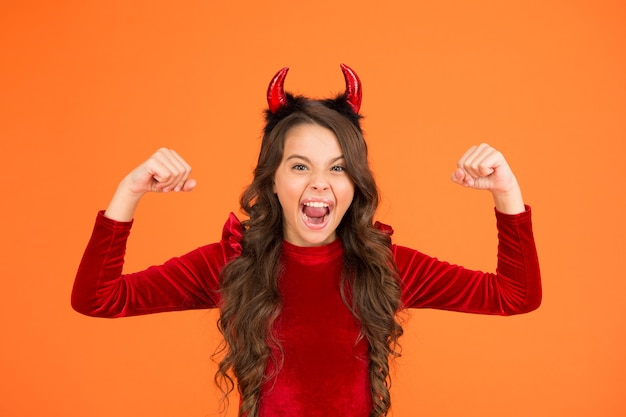 Energy and power. little girl red horns celebrate halloween. carnival concept. child with imp style accessory halloween party. trick or treat. halloween costumes designed after supernatural figures.