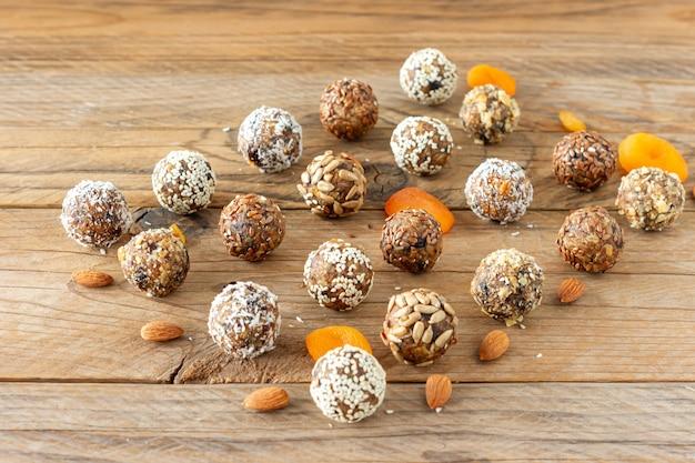 나무 탁자에 건강한 재료를 넣은 에너지 단백질 공. 대추야자, 아몬드, 아마, 씨앗으로 만든 집.
