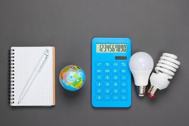 에너지 절약 분석. 전구, 노트북, 회색 지구본 계산기